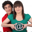 Two teenagers embracing and holding an at sign - Stock Photo
