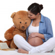 Pregnant woman sat with large teddy bear — Stock Photo