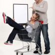 Playful couple with shopping trolley — Stock Photo