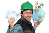 Laborer holding a globe, a green plant and twenty Euros bills — Stock Photo