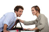 Young couple competing with laptops — Stock Photo