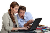 Shocked couple pointing at a laptop — Stock Photo