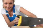 Woman sawing wood — Stock Photo