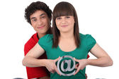 Two teenagers embracing and holding an at sign — Stock Photo