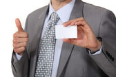Businessman thumb up showing business card — Stock Photo