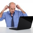 Bald businessman with laptop and headphones — Stock Photo