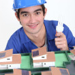 Stock Photo: An electrician lighting a miniature.
