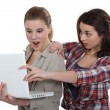 Two shocked girls looking at laptop — Stock Photo