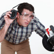 Stock Photo: Carpenter lifting his earmuff to listen to you