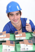 An electrician lighting a miniature. — Stock Photo