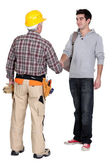 A construction worker and his trainee shaking hands. — Stock Photo