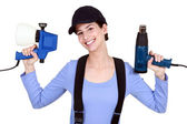 Woman holding paint sprayer and heat gun — Stock Photo