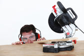 Craftsman cutting a wooden board with an electric saw — Stock Photo