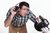 Carpenter lifting his earmuff to listen to you — Stock Photo