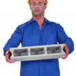 Builder carrying heavy building block - Stock Photo