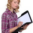 Attractive woman writing in a folder — Stock Photo #14732991