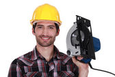 Man proudly holding electric saw — Stock Photo