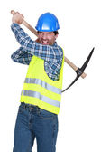 Aggressive labourer holding a pickaxe — Stock Photo