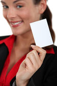 Smiling young businesswoman showing business card — ストック写真