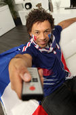 French football supporter holding television remote control — Stock Photo
