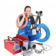 Stock Photo: Female labourer speaking on mobile telephone surrounded by equipment