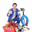 Plumber showing cellphone, studio shot - Stock Photo