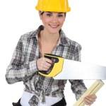 Cute female carpenter using handsaw — Stock Photo #14899155