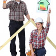 Carpenters holding a hammer and an energy efficiency rating sign - Stock Photo