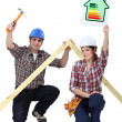 A couple of carpenters promoting energy savings. — Stock Photo