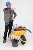 Mason stood by wheelbarrow pointing — Stock Photo