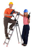 Tradesman posing with his young apprentice — Stock Photo