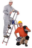 Painter on a ladder and crouching electrician — Stock Photo