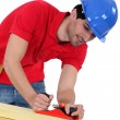 Construction worker planing wood - Stock Photo