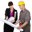 Tradesman consulting with an engineer - Stock Photo