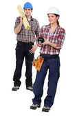 Two carpenters stood with piggy-bank — Stock Photo