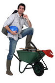 Tradesman with his foot propped up on a wheelbarrow — Stock Photo