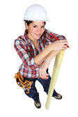 Female carpenter marking wood with pencil — Stock Photo