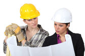 Construction worker looking at a plan with an engineer — Stock Photo