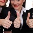 Three coworkers giving the thumb up. - Stock Photo