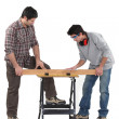Stock Photo: Father and son securing plank of wood
