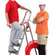 Two plumbers stood with ladder and copper pipe — Stock Photo #14915121