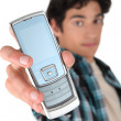 Teenage boy holding out mobile telephone - Stock Photo