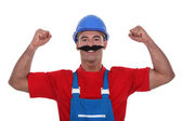 Muscular tradesman wearing a fake moustache — Stock Photo