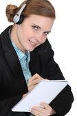 Receptionist skriver i en anteckningsbok — Stockfoto