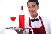Male waiter with wine on tray — Stock Photo