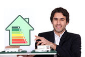 Architect holding model house and energy rating card — Stock Photo