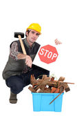 Builder kneeling by recycle box — Stock Photo