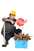 Labourer holding a stop sign while squatting before a bin full of wood — Stock Photo