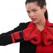 Businesswoman wearing boxing gloves — Stock Photo #14936527