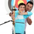 Man and a teenager practicing archery - Lizenzfreies Foto